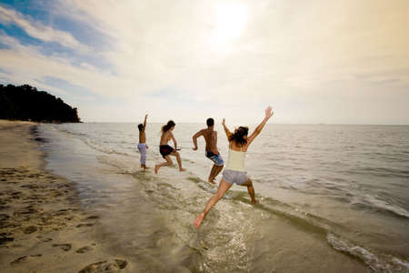 group of friends having fun jumping into the sea on sunset Stock Photo - 2640779