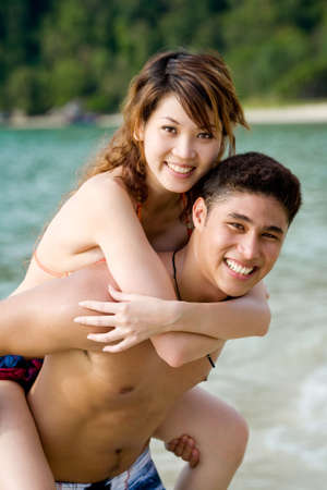 couple carrying piggyback on a tropical beach Stock Photo - 2640806