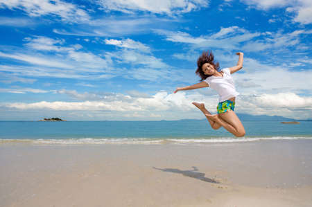 lifestyle: young beautiful girl jumping gracefully at the beach Stock Photo