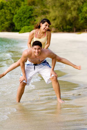 woman hop from back of the guy by  the beach Stock Photo - 2680894