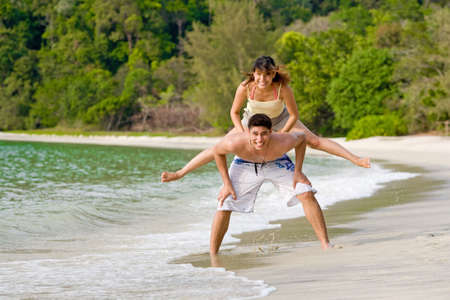 couple having fun hopping on the beach photo