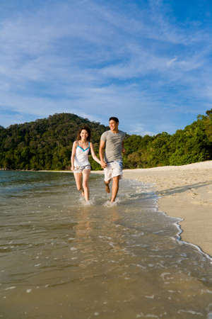 loving young couple running on the beautiful tropical beach Stock Photo - 2680896