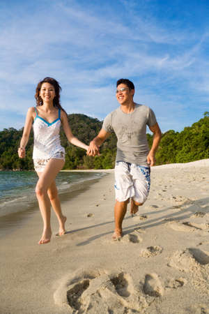 loving young couple enjoying themselves running along the beach happily Stock Photo - 2680900