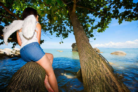 lonely angel hiding on a tree looking out to the sea Stock Photo - 2774439