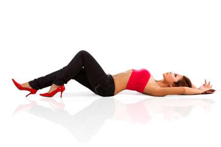tacones rojos: hermosa mujer de curvas de color rojo y tacones de color rojo arriba del tubo acostado en el suelo  Foto de archivo