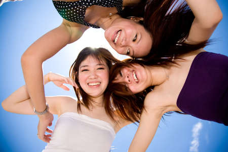 three young happy girls fooling around looking down with sun and blue sky behind Stock Photo