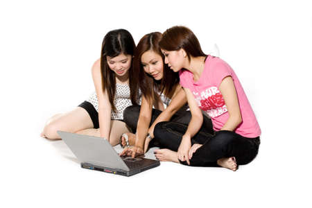 three young friends chatting online on a notebook computer sitting on the floor Stock Photo
