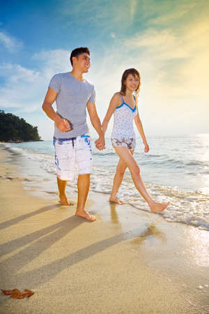 happy couple walking along the sunset golden sand beach Stock Photo