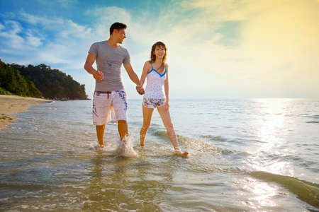 honeymoon couple: couple holding hands walking along the sunset beach Stock Photo