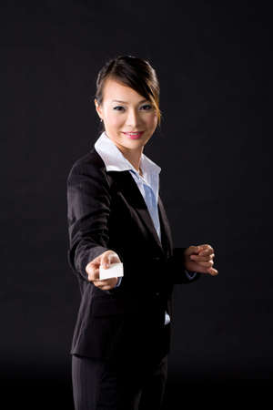 woman in a corporate business suit presenting her business card on a black background photo