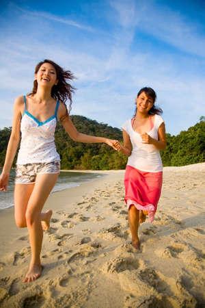 two girl friends having fun running along the sunset beach