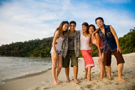 a group of male and female friends by the beautiful tropical beach Stock Photo
