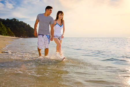 happy young couple holding hands walking along the romantic sunset beach Standard-Bild