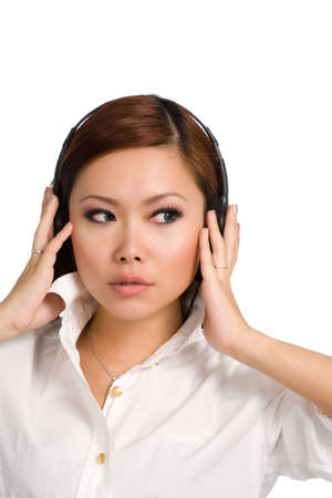 contented: beautiful asian woman with headphones looking to the side. In white shirt, head and shoulders