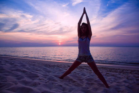 woman relaxing by doing yoga exercise on the sunset beach