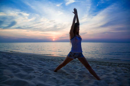 relaxing woman doing yoga on the sunset beach