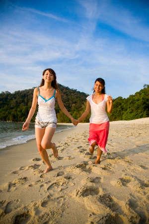 two girls best friend holding hands having fun running along the beach Standard-Bild