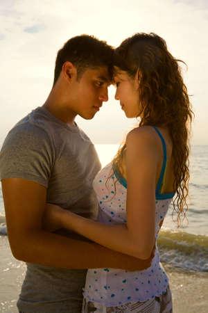 loving couple hugging each other at the romantic sunset beach Standard-Bild