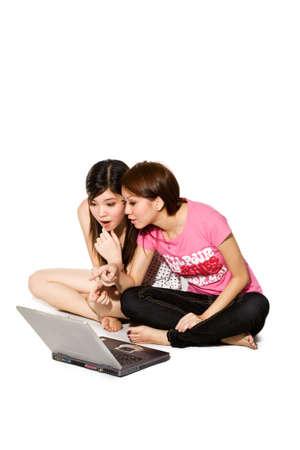cross leg: dos j�venes ni�a de mensajer�a instant�nea en un ordenador port�til y apuntando como si discutir algo