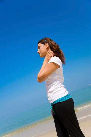 asian woman relaxing looking far away on the bright blue sky standing by the beach photo