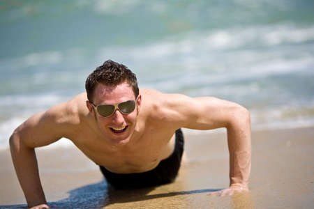beach hunk: young caucasian hunk smiling and getting up from the sandy beach