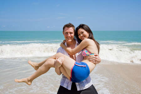 strong handsome caucasian man carrying a beautiful asian girl Stock Photo - 2997165