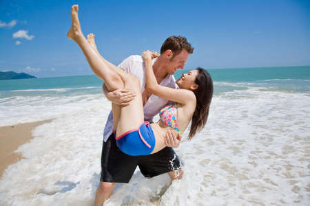 strong handsome caucasian man carrying a beautiful asian girl