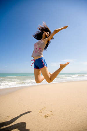 joyfully: young woman leaping joyfully in the air