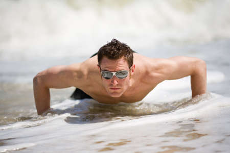 beach hunk: young caucasian hunk up from the sandy beach with sunglasses