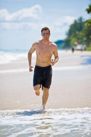 beach hunk: caucasian man running on the beach with sunglasses