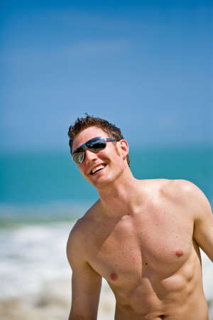 beach hunk: young handsome caucasian man with sunglasses LANG_EVOIMAGES
