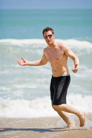 caucasian man running on the beach with sunglasses photo