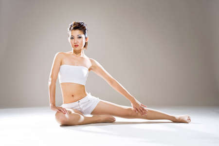 young asian woman sitting on the floor with one leg stretch photo