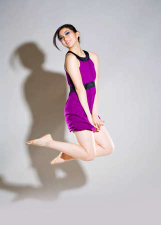 joyfully: young woman in purple dress jumping joyfully LANG_EVOIMAGES