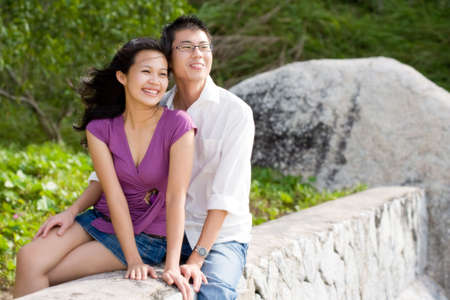 sweethearts: happy young couple sitting on the fence enjoying the scenery