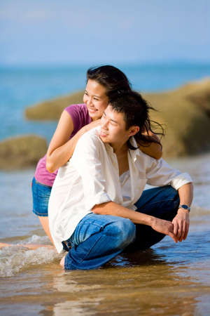 loving young couple hugging and squating at the beach