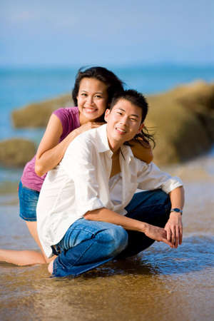 asian young couple squating at the beach happily