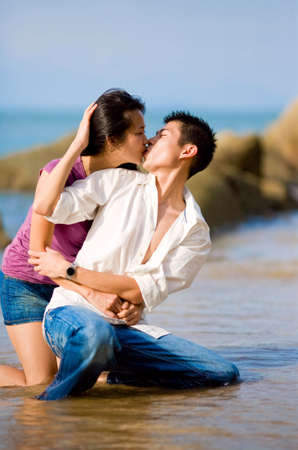 loving young couple kissing while squating by the beach