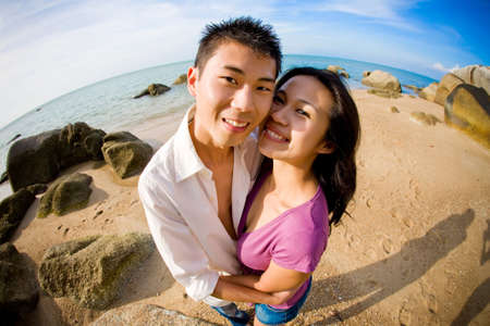 happy couple having fun during vacation on the beach smiling towards camera Stock Photo