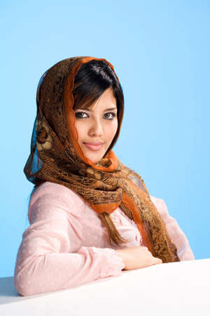 smiling muslim young woman in head scarf and traditional wear