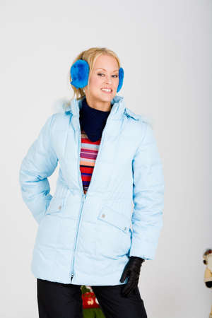 muff: happy blond girl in a winter coat and ear muffs