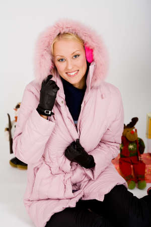 happy blond girl in a pink coat and ear muffs photo