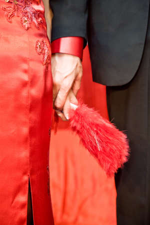 newly wed asian chinese bride in traditional red cheongsam dress holding hands with the groom on their wedding Standard-Bild