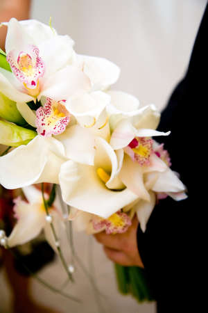 groom holding a bouquet of orchids and lilies photo