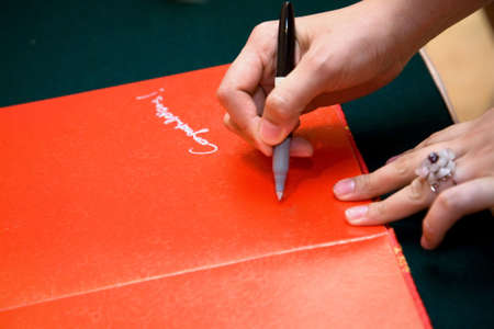 hand of a guest holding a pen writing on a red chinese wedding guests book photo
