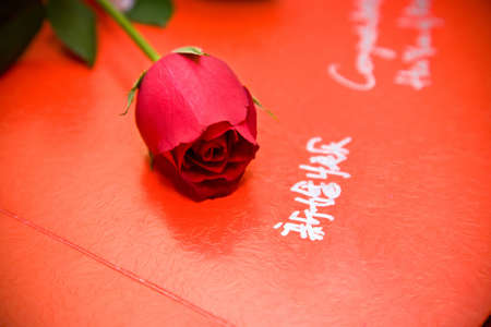 a red guests book of a chinese culture wedding with greetings words and a rose on it photo