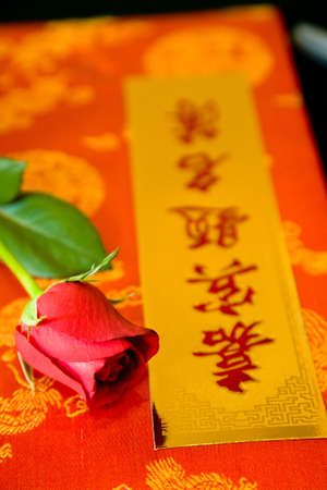a red guest book of traditional chinese wedding with a red rose on it  photo