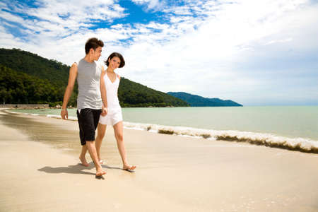 loving asian young couple holding hands walking along the beach happily
