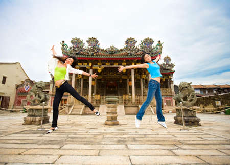 two asian girls friend jumping happily when travel to the heritage building of chinese temple photo