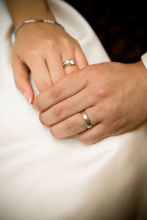 bride and groom holding hands with wedding rings on it Stock Photo